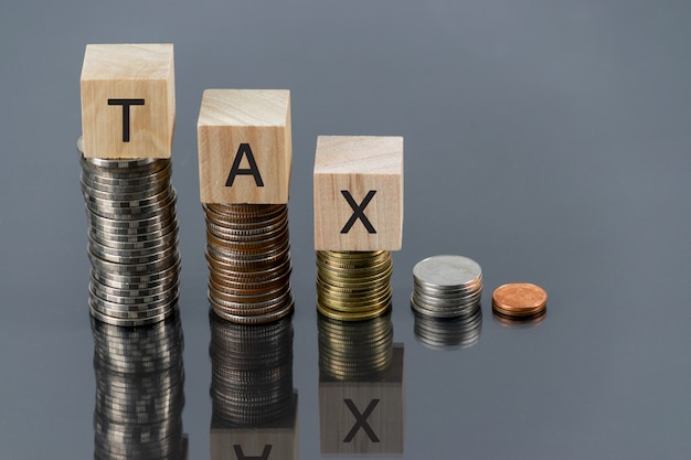 Налоговой деревянный кубик со стопкой монет на столе с отражателем