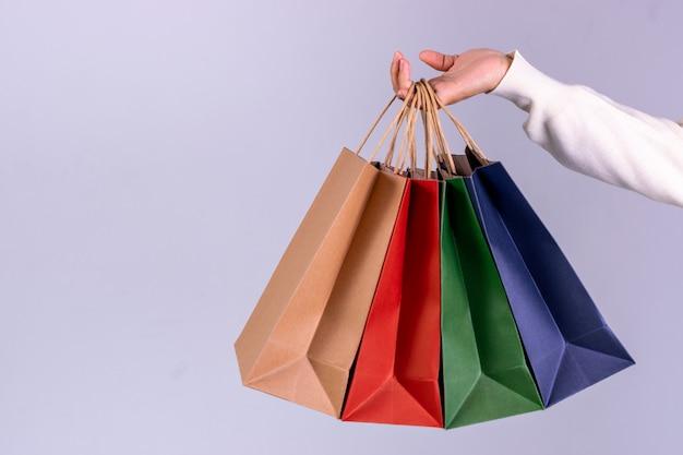 コピースペースを持つ紙袋を持つ女性の手。ブラックフライデーまたはサイバーマンデーのコンセプト。