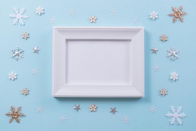 クリスマスと冬のコンセプト。明るい青の背景にフォトフレームとスノーフレーク。