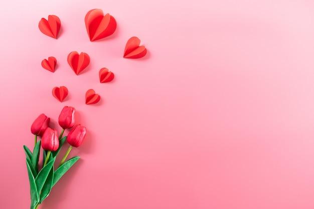 ピンクの背景に赤い紙の心と赤いチューリップの花。バレンタインデー、女性の日、母の日。