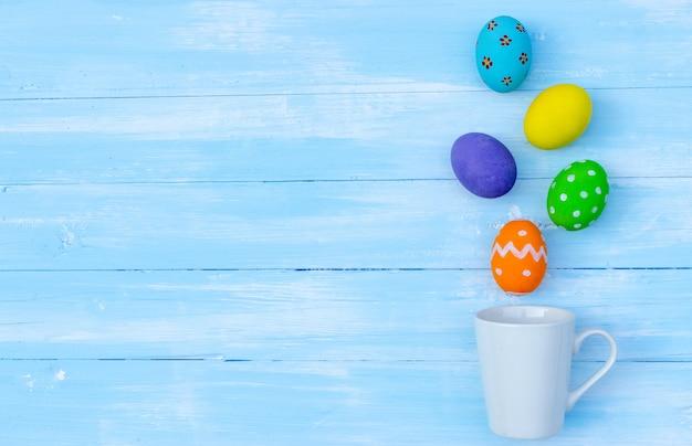 カラフルなイースターエッグは青い木の上の白いコーヒーカップからはねかける