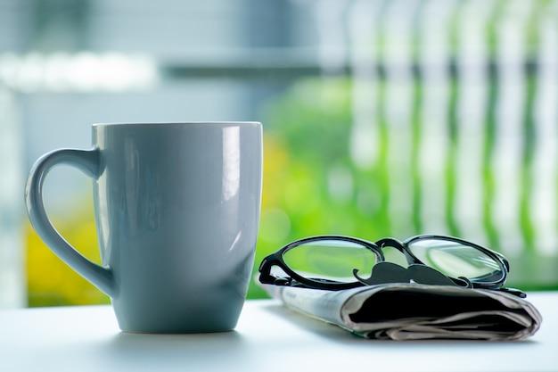 С днем отца. кофейная чашка, очки, усы и газеты на столе на фоне зеленых боке.
