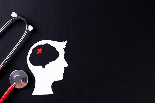 聴診器でカット紙の脳の平面図です。世界脳腫瘍デー。