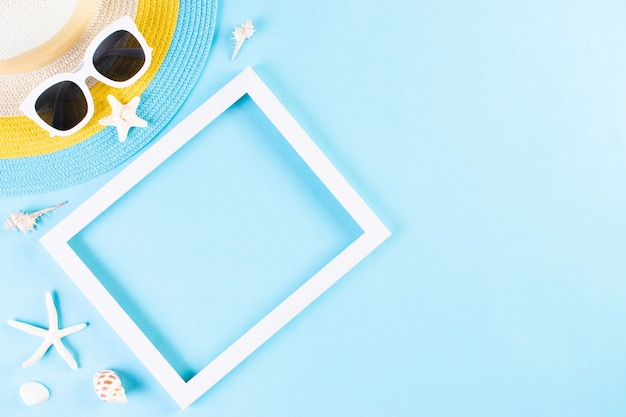 Лето или отпуск концепции. пляж шляпу и солнцезащитные очки с фоторамкой на светло-синем фоне.