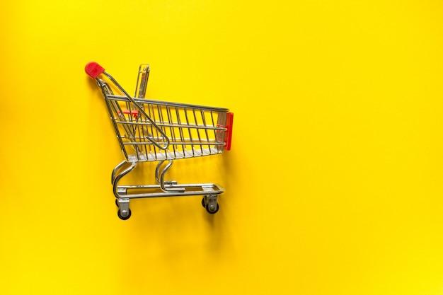 黄色の背景にショッピングカートのトロリー。