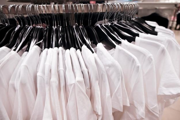 Магазин одежды. белые футболки на вешалке.