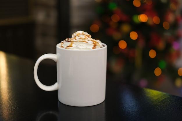 クリスマスツリーボケ花輪の背景にカフェでココアまたはキャラメルシロップとクリームとコーヒーと白いマグカップ。カップにトッピングしたカプチーノまたはラテ。