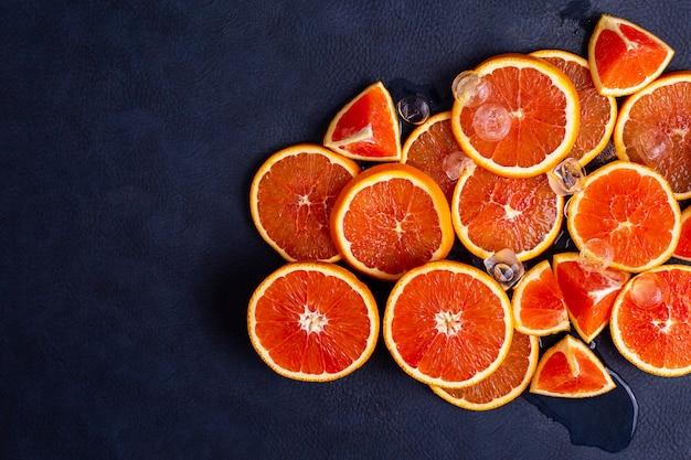 新鮮な赤オレンジまたはグレープフルーツと青の古典的な背景に氷。熱帯の柑橘系の果物。美しいカットジューシースライス。スタジオ撮影