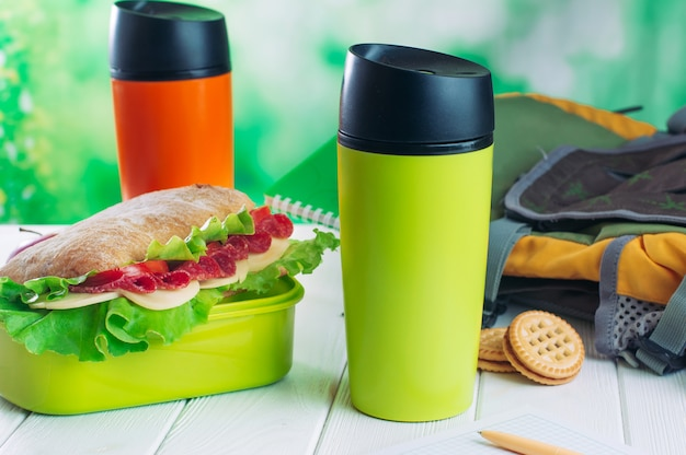 Термос кружки возле коробки для завтрака и рюкзак на деревянный стол