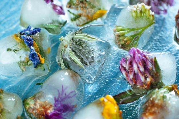 ガラスの背景にハート形のアイスキューブの野の花