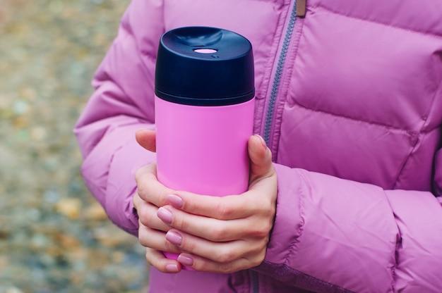 外を歩くサーモマグカップを保持している女性
