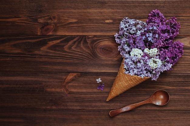 木のスプーンの近くのライラック色の花とアイスクリームワッフルコーン