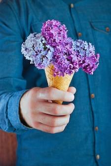 ライラック色の花とアイスクリームワッフルコーンを持つ男性の手