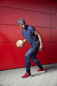 若い男がバスケットボールをする