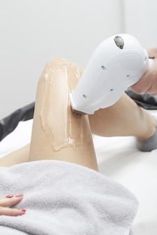 Косметолог удаление волос молодой женщины с лазером