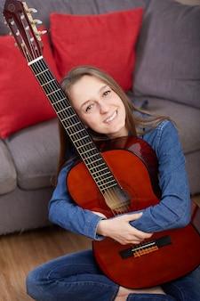 女性が自宅でギターを弾く