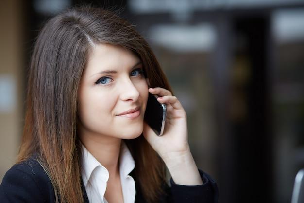 Молодая коммерсантка говоря к черни в городской среде