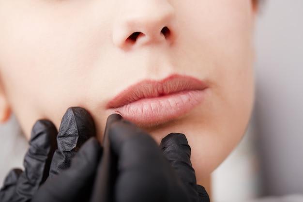 Косметолог наносит перманентный макияж на губы