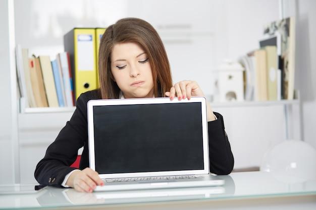 Деловая женщина показывает пустой экран своего ноутбука