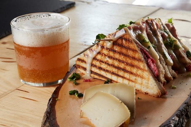 Бутерброд с сыром на деревянном подносе с пивом