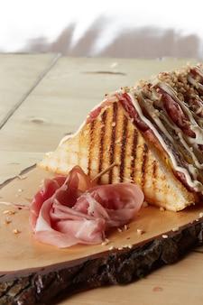 Клубный сэндвич на деревянном подносе