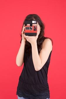 女性はインスタントカメラで写真を撮る