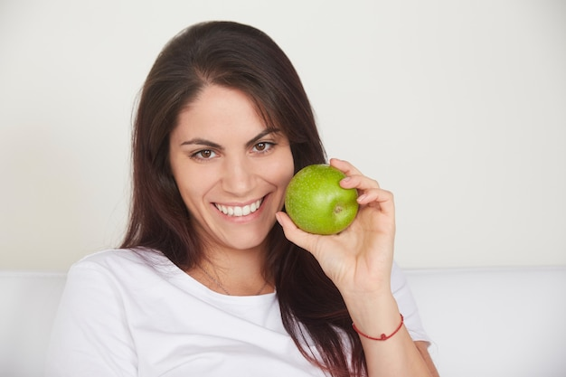 Милая женщина держа зеленое яблоко