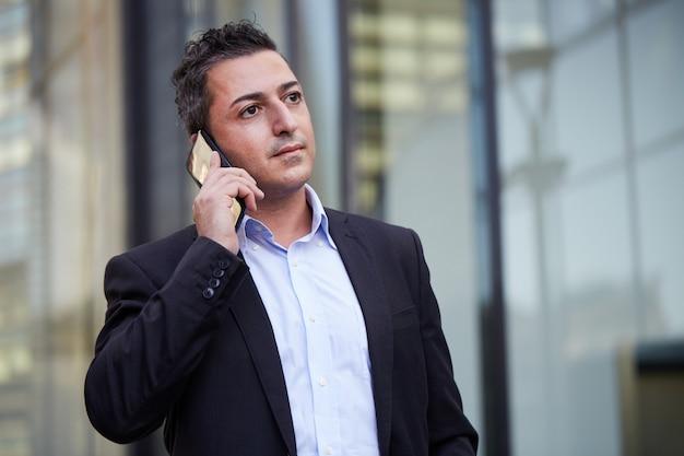 Бизнесмен разговаривает по мобильному в городской среде