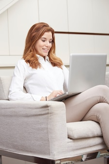 Красивая женщина с ноутбуком на диване
