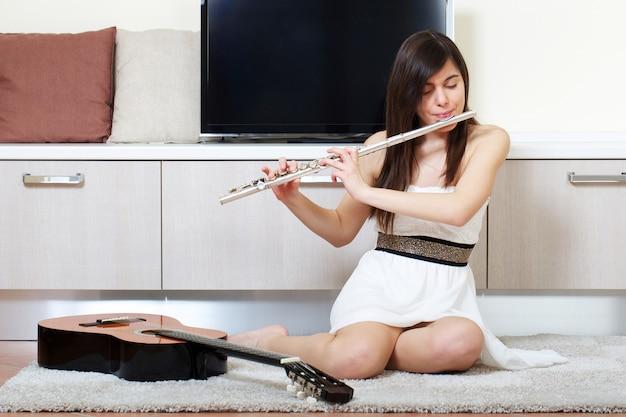 女性が自宅で横フルートを演奏します。