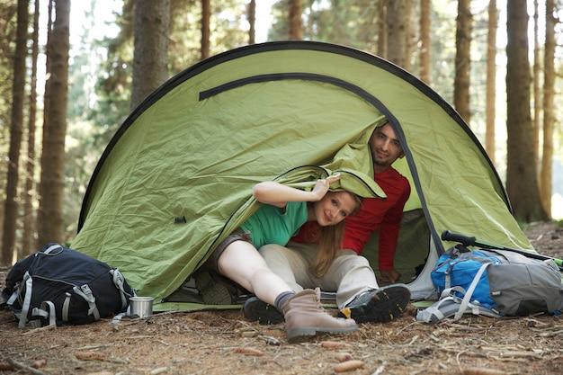 ハイカーのカップルはテントで休む