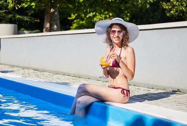 リラックスして、スイミングプールでカクテルを飲む女性