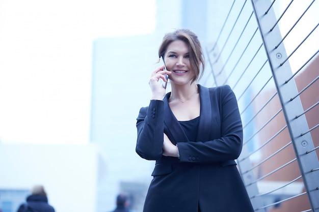 都市環境でモバイルと話すビジネスウーマ