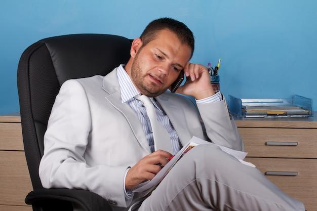 Бизнесмен разговаривает по мобильному в офисе