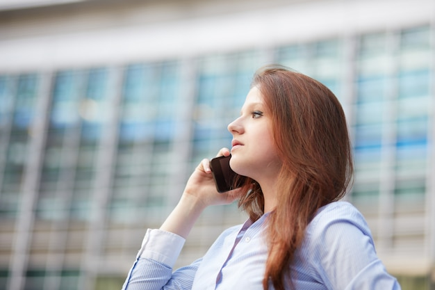 都市環境で携帯電話に話している実業家