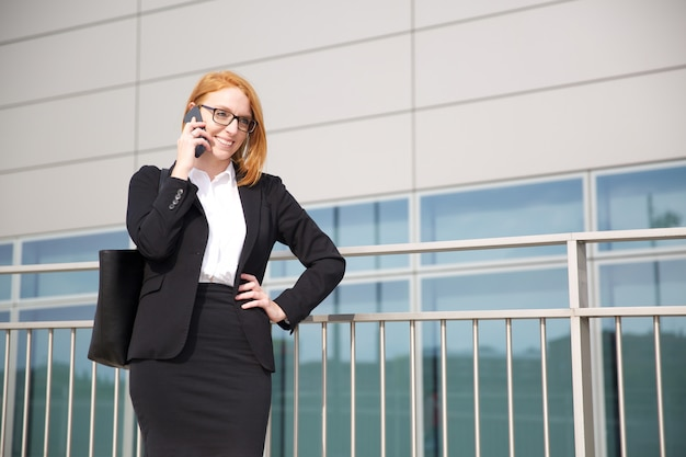 Деловая женщина разговаривает по мобильному телефону в городской среде