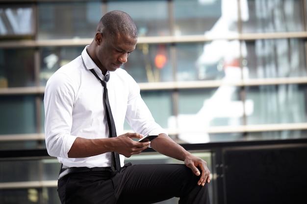 都市環境でのモバイルとラップトップで働くビジネスマン