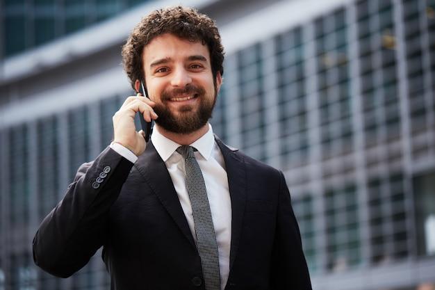 都市の携帯電話に話している実業家