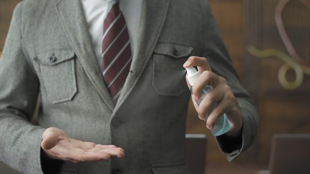 消毒スプレー作業を示す男性の手のクローズアップ