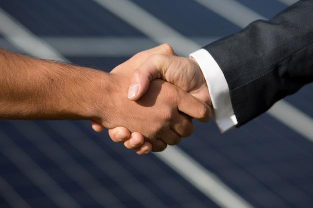 Согласие рукопожатие, солнечные панели на фоне.