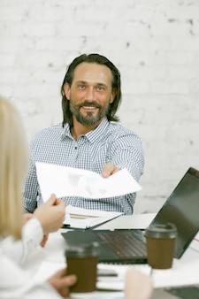 Улыбающийся бизнесмен передает бумажный бланк своему коллеге