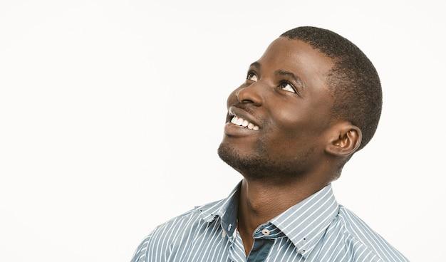 Афро-американский красавец зубастые улыбки, глядя вверх и в сторону, темнокожий молодой парень в синей полосатой рубашке