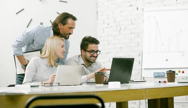 Совместная работа коллег чтения новостей вместе на компьютере в офисе света