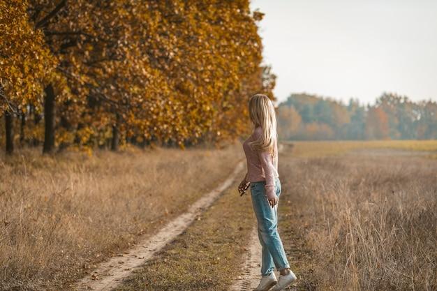 Вид сзади молодой женщины в повседневной одежде на цыпочках на природе, очаровательная молодая блондинка гуляет по грунтовой дороге возле осеннего леса