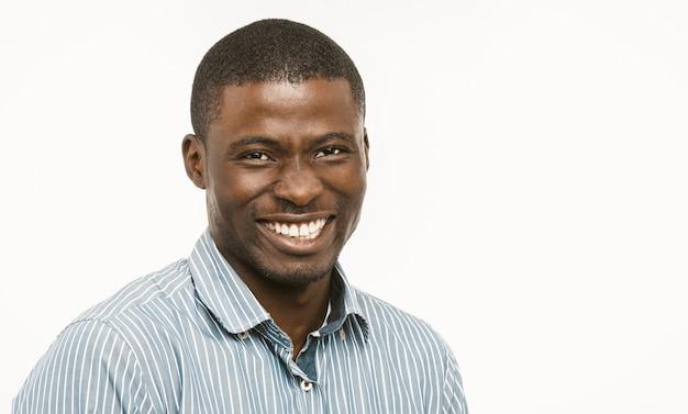 Красивый африканский парень с белозубой улыбкой смотрит в камеру, темнокожий хорошо одетый молодой человек