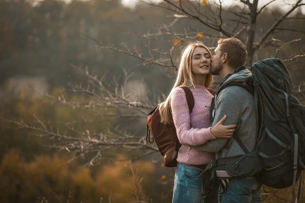 Молодой человек целует свою красивую белокурую жену на улице