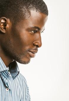 Вид профиля афро-американского человека в синей полосатой рубашке.