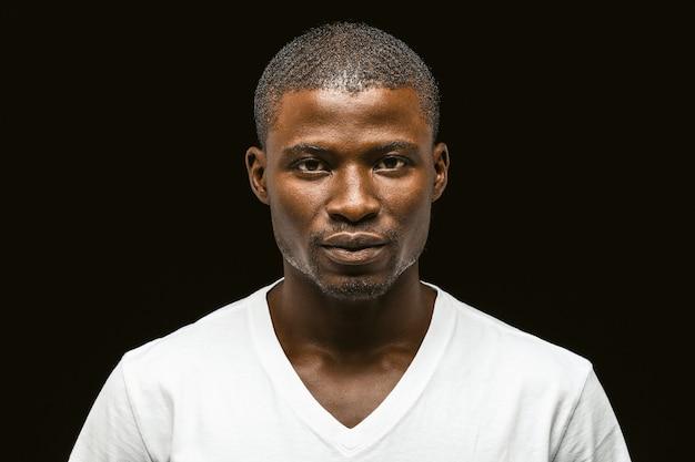 Серьезный афроамериканец смотрит в камеру, привлекательный темнокожий молодой парень в белой футболке