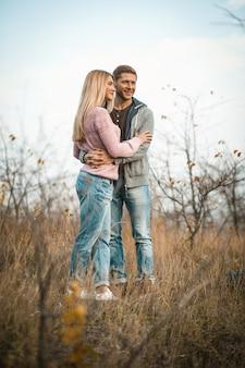 Обниматься пара, улыбаясь стоя на осенней траве на открытом воздухе, молодые парни обнимаются в природе на фоне голубого неба