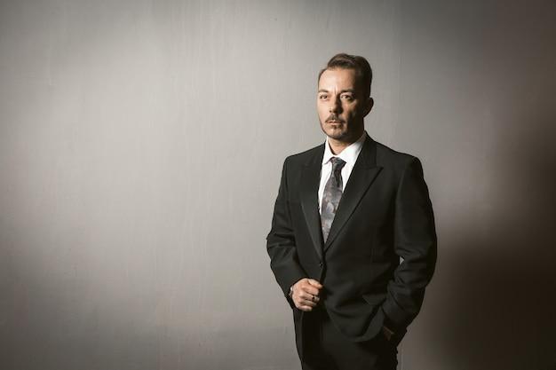 Заботливый бизнесмен в положении костюма изолированный на серой предпосылке. умный уверенный предприниматель в черной элегантной торжественной одежде думает о новых бизнес-идеях